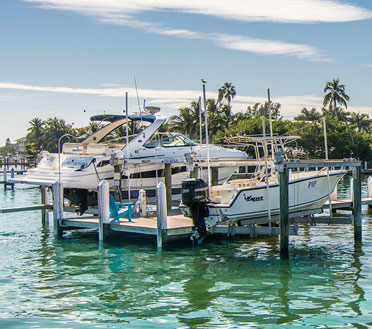 Two private boats suspended in air by a boat lift in Southwest Florida constructed by Florida Marine Construction